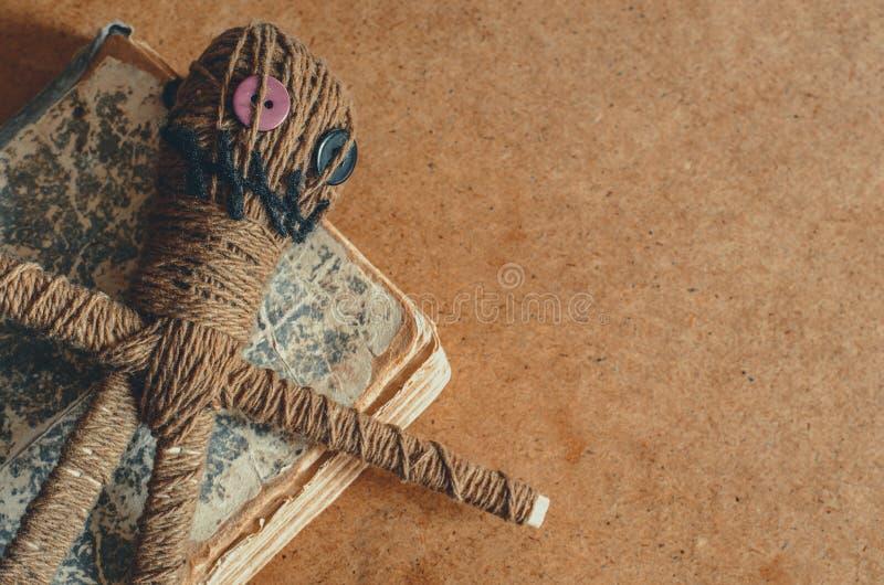 Κούκλα βουντού με τις βελόνες και παλαιό βιβλίο στο τραχύ κατασκευασμένο υπόβαθρο στοκ φωτογραφίες με δικαίωμα ελεύθερης χρήσης