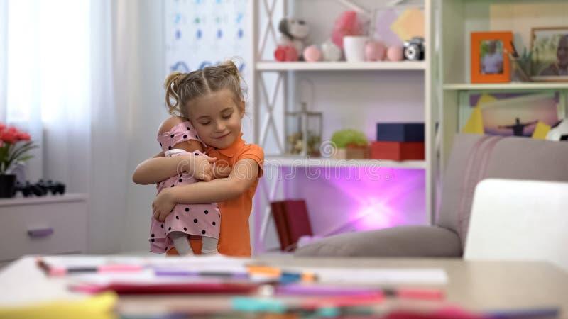 Κούκλα εκμετάλλευσης κοριτσιών, που αγκαλιάζει το αγαπημένο παιχνίδι, κοριτσίστικος ελεύθερος χρόνος, ευτυχία παιδικής ηλικίας στοκ εικόνα με δικαίωμα ελεύθερης χρήσης