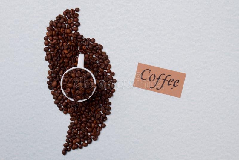 Κούπα καβουρντισμένων κόκκων καφέ σε ένα σωρό στοκ εικόνες