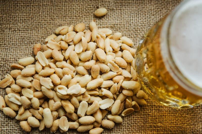 Κούπα με την μπύρα και αλατισμένα φυστίκια στον πίνακα στοκ φωτογραφία με δικαίωμα ελεύθερης χρήσης