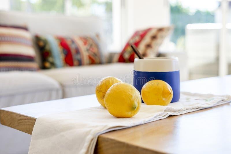 Κούπα τσαγιού με το ξύλινο κουτάλι και λεμόνια στον πίνακα στοκ εικόνα με δικαίωμα ελεύθερης χρήσης