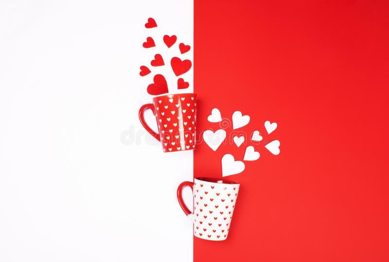 Κούπες με τις διεσπαρμένες καρδιές κόκκινος και άσπρος στοκ εικόνα