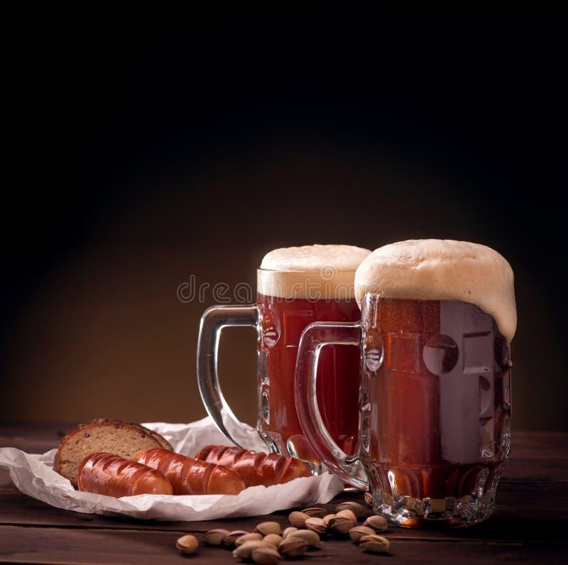 Κούπες της μπύρας με τα πρόχειρα φαγητά στοκ φωτογραφία με δικαίωμα ελεύθερης χρήσης
