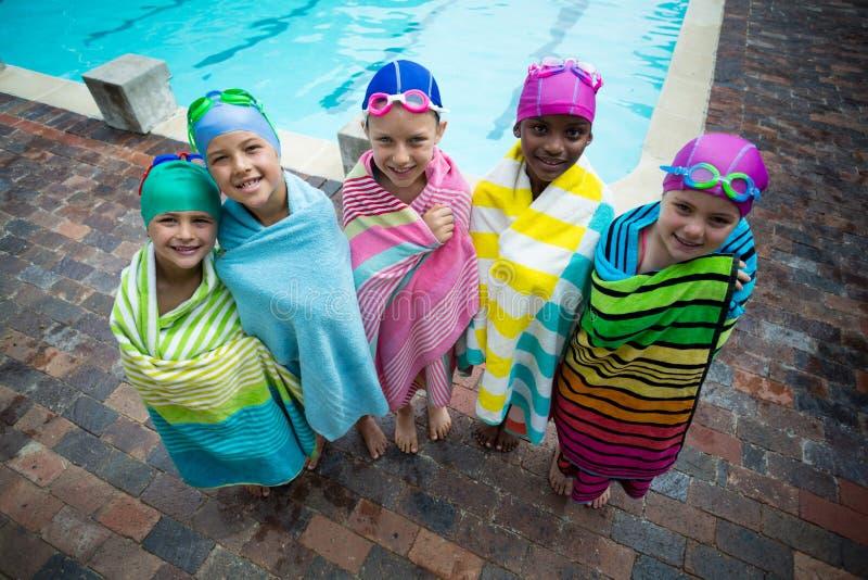 Κολυμβητές που τυλίγονται στις πετσέτες που στέκονται στο poolside στοκ φωτογραφίες με δικαίωμα ελεύθερης χρήσης