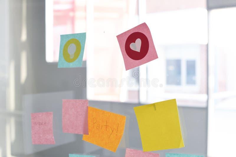 Κολλώδες υπόμνημα υπενθυμίσεων σημειώσεων που ράβεται στο γραφείο τοίχων γυαλιού στοκ εικόνα με δικαίωμα ελεύθερης χρήσης