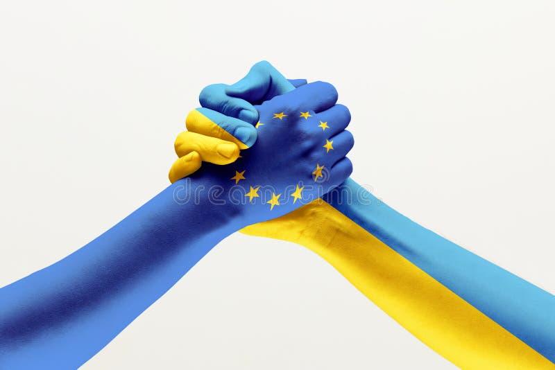 Δύο χέρια Σημαία της Ευρωπαϊκής Ένωσης Σημαία της Ουκρανίας στοκ εικόνα με δικαίωμα ελεύθερης χρήσης