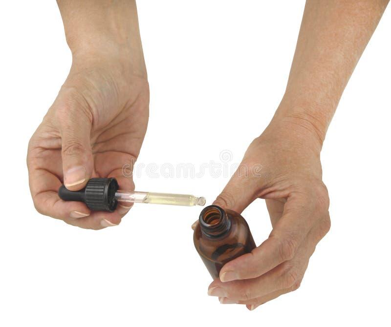 Κράτημα ενός Dropper ουσιαστικών πετρελαίων μπουκαλιού στοκ εικόνα με δικαίωμα ελεύθερης χρήσης