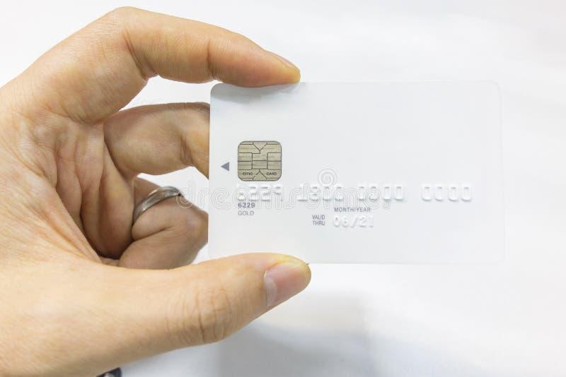 Κράτημα μιας άσπρης πιστωτικής κάρτας στο χέρι του στοκ φωτογραφίες με δικαίωμα ελεύθερης χρήσης