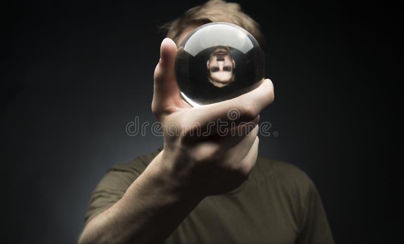 Κράτημα μιας σφαίρας κρυστάλλου στοκ εικόνες