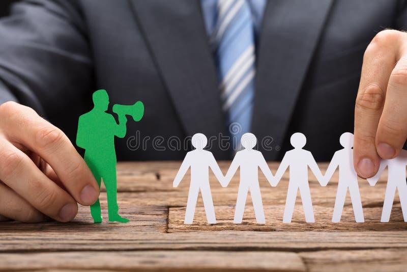 Κράτημα πράσινου Paperman μιλώντας μέσω Megaphone με την ομάδα στοκ εικόνα