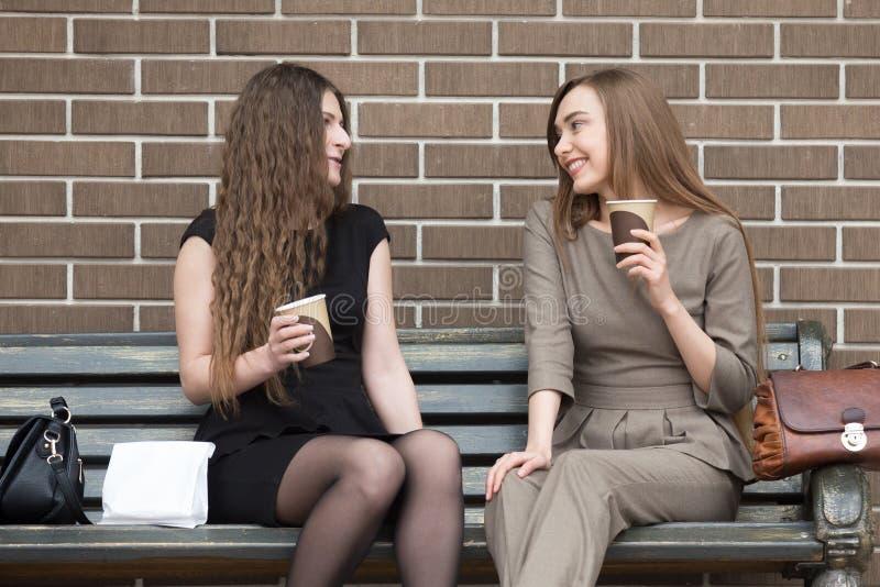 Κράτημα δύο το νέο όμορφο γυναικών παίρνει μαζί τον καφέ και να κουβεντιάσει στοκ εικόνα με δικαίωμα ελεύθερης χρήσης