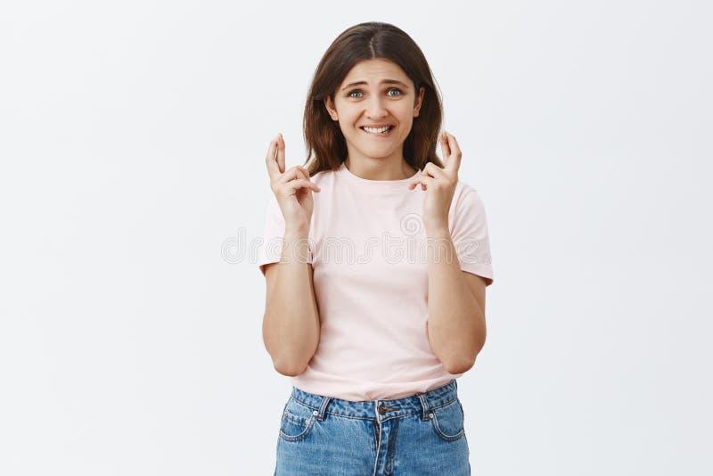 Κράτηση της πίστης στο καλό αποτέλεσμα Έντονη ανησυχημένη ελκυστική γυναίκα σπουδαστής στα καθιερώνοντα τη μόδα δάχτυλα εκμετάλλε στοκ εικόνα με δικαίωμα ελεύθερης χρήσης