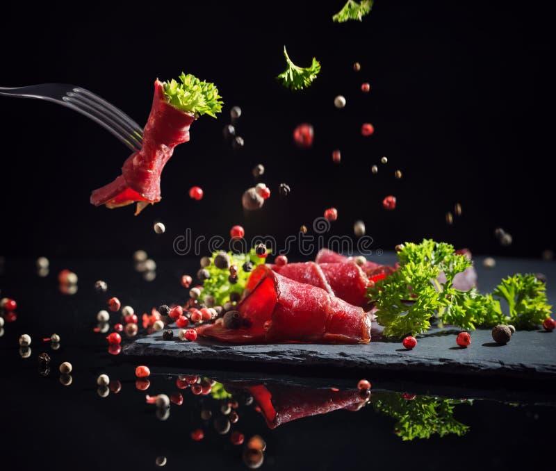 Κρέας που τεμαχίζεται με τα πράσινα σε ένα μαύρο υπόβαθρο στοκ εικόνες με δικαίωμα ελεύθερης χρήσης