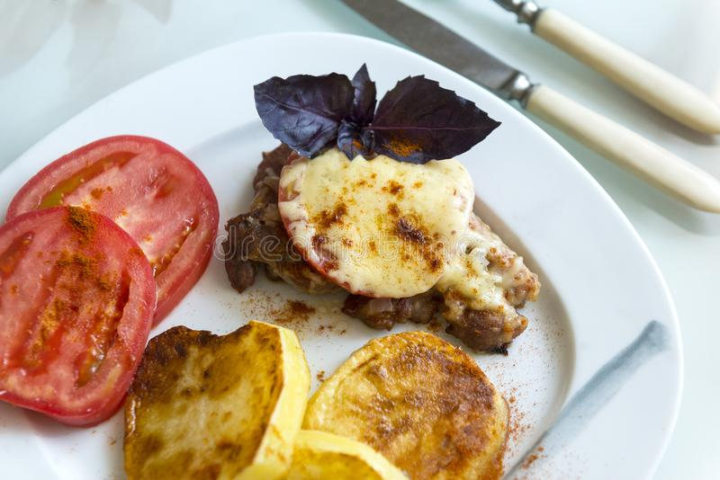 Κρέας που ψήνεται κάτω από το τυρί με την ντομάτα και τις πατάτες με τα καρυκεύματα επάνω στοκ εικόνες