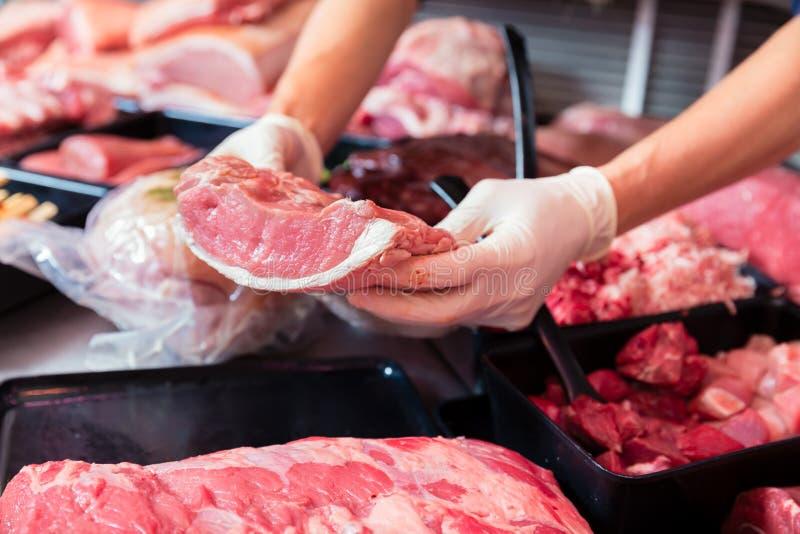 Κρέας σε μια επίδειξη καταστημάτων χασάπηδων που υποβάλλεται από τη γυναίκα πωλήσεων στοκ εικόνα