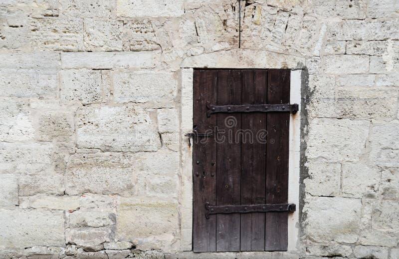 Κρέμα και άσπρος παλαιός τοίχος υποβάθρου σύστασης ασβεστόλιθων τούβλου εγχώριος με την παλαιά σκοτεινή ξύλινη πόρτα Πίσω επίπεδο στοκ εικόνες με δικαίωμα ελεύθερης χρήσης