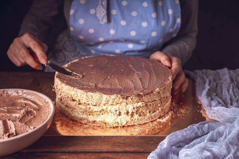 Κρέμα σοκολάτας με μαχαίρι στα γυναικεία χέρια στοκ φωτογραφία