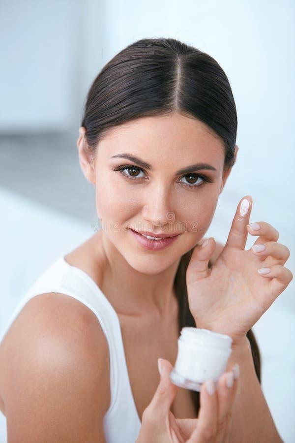 Κρέμα φροντίδας δέρματος προσώπου ομορφιάς Κορίτσι με την του προσώπου κρέμα στο δάχτυλο στοκ εικόνες