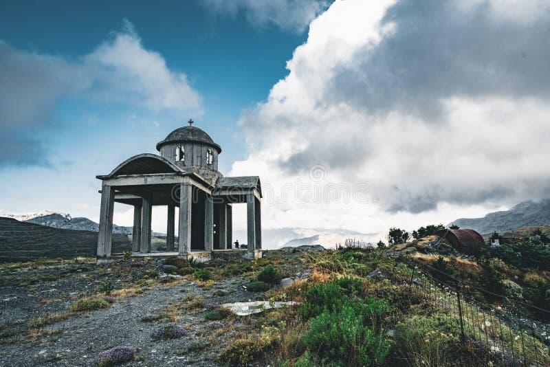Κρήτη, Ελλάδα, μικρή ατελής εκκλησία, καταπληκτικό παρεκκλησι που εγκαταλείπεται στις πέτρες και τους βράχους βουνών με το μπλε ο στοκ εικόνες