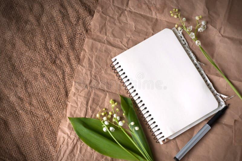 Κρίνος των κοιλάδων, του κενών σημειωματάριου και των μανδρών sackcloth στοκ φωτογραφία με δικαίωμα ελεύθερης χρήσης