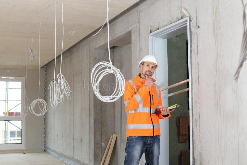 Κρίσιμος ειδικός εκτιμητής κατασκευής που ελέγχει μια περιοχή constructin στοκ φωτογραφίες