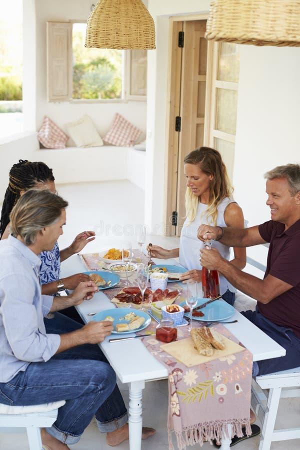 Κρασί ανοίγματος οικοδεσποτών για τους φιλοξενουμένους γευμάτων σε έναν πίνακα σε ένα patio στοκ εικόνα με δικαίωμα ελεύθερης χρήσης