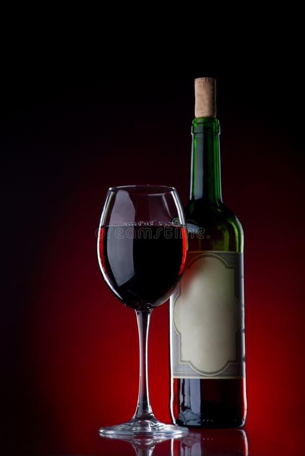 Κρασί και γυαλί σε ένα μαύρο κλίμα με το κόκκινο φως στοκ εικόνες