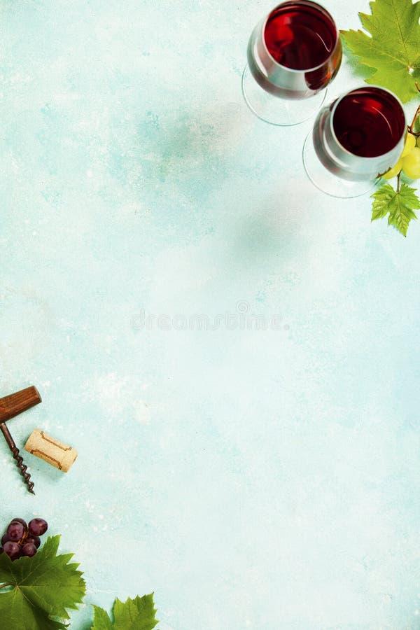 Κρασί και σταφύλια πέρα από το μπλε εκλεκτής ποιότητας υπόβαθρο στοκ εικόνες