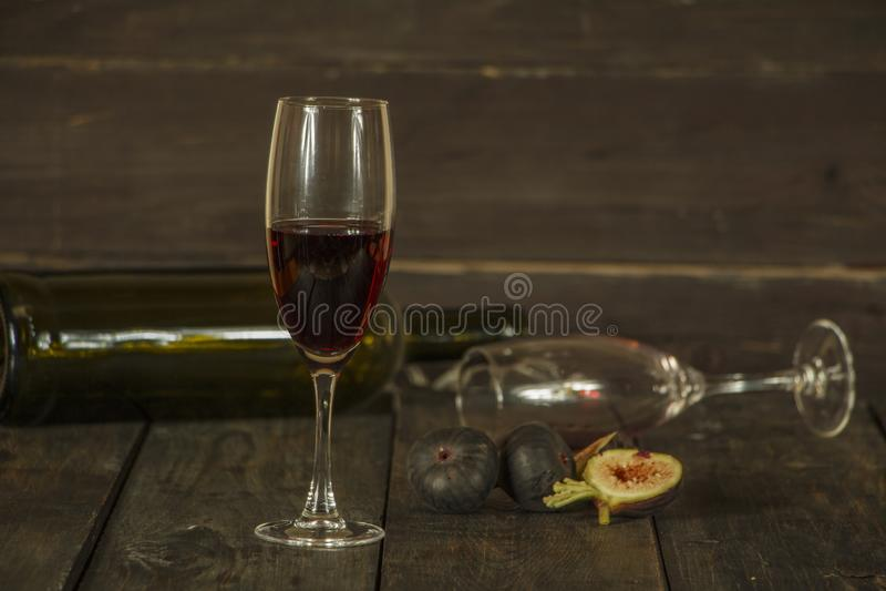 Κρασί σε ένα γυαλί ένα κενό μπουκάλι των σύκων σε ένα σκοτεινό ξύλινο υπόβαθρο Ένα ποτήρι του κρασιού σε έναν ξύλινο πίνακα στοκ φωτογραφίες