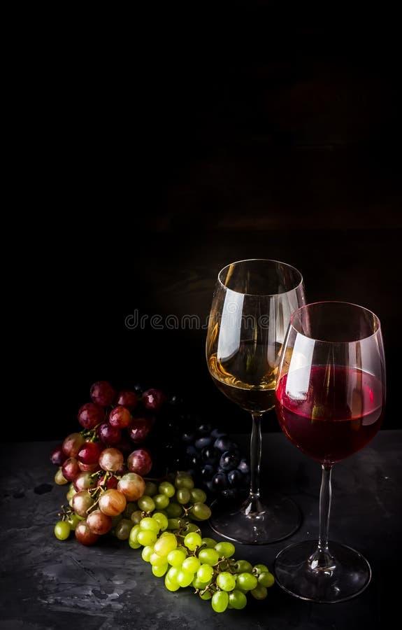 Κρασί στα γυαλιά και τους διαφορετικούς τύπους σταφυλιών στο σκοτεινό υπόβαθρο στοκ εικόνες με δικαίωμα ελεύθερης χρήσης