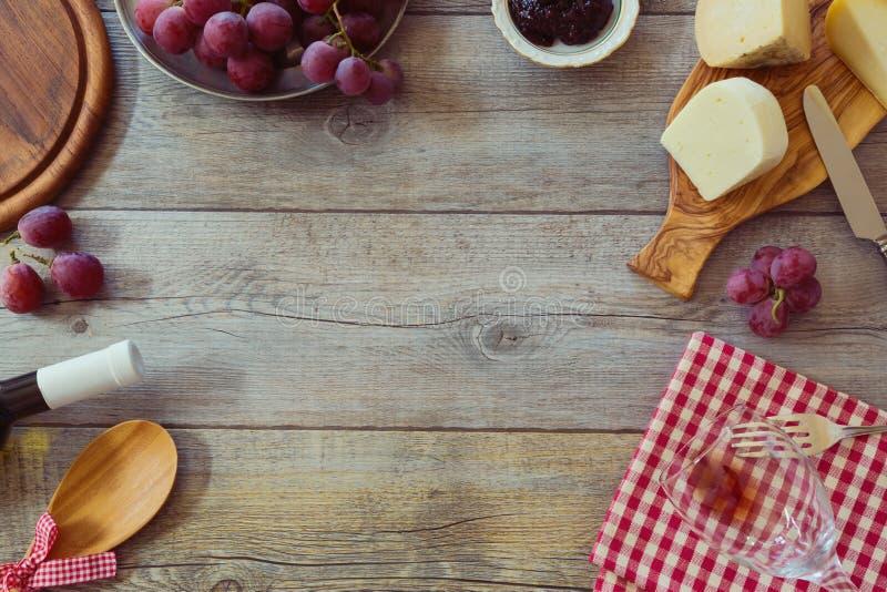Κρασί, τυρί και σταφύλια στον ξύλινο πίνακα Άποψη άνωθεν με το διάστημα αντιγράφων στοκ εικόνες
