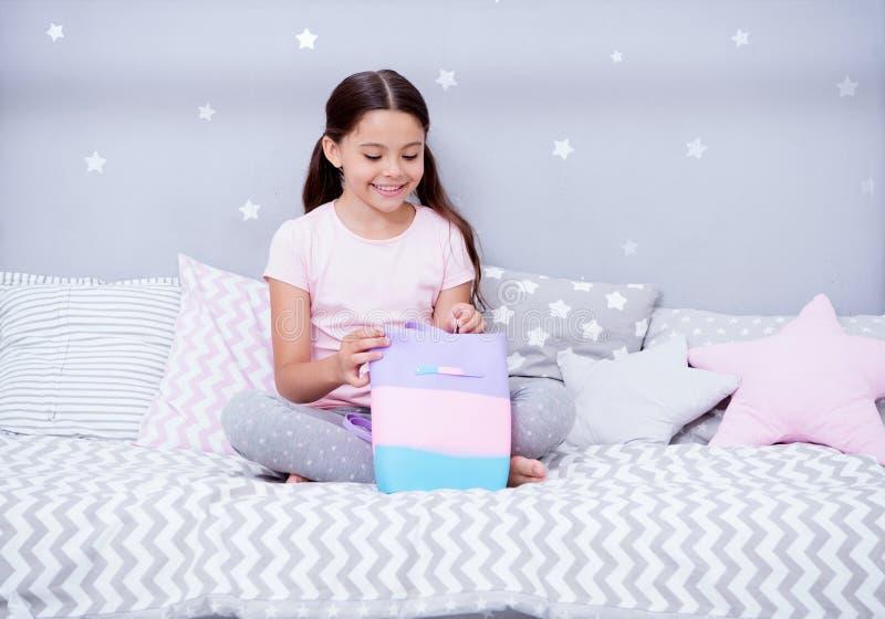 Κρατά τους θησαυρούς της σε εκείνη την τσάντα Το παιδί κοριτσιών κάθεται στο κρεβάτι στην κρεβατοκάμαρά της Το παιδί προετοιμάζετ στοκ φωτογραφία