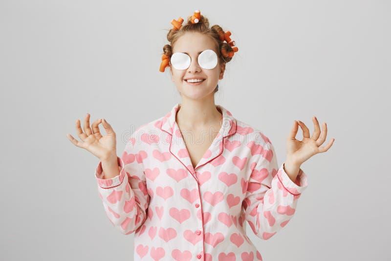 Κρατήστε ήρεμος και κατασταθείτε όμορφος Χαριτωμένη γοητευτική γυναίκα στα ρόλερ τρίχας, τις πυτζάμες και τα μαξιλάρια βαμβακιού  στοκ φωτογραφία με δικαίωμα ελεύθερης χρήσης