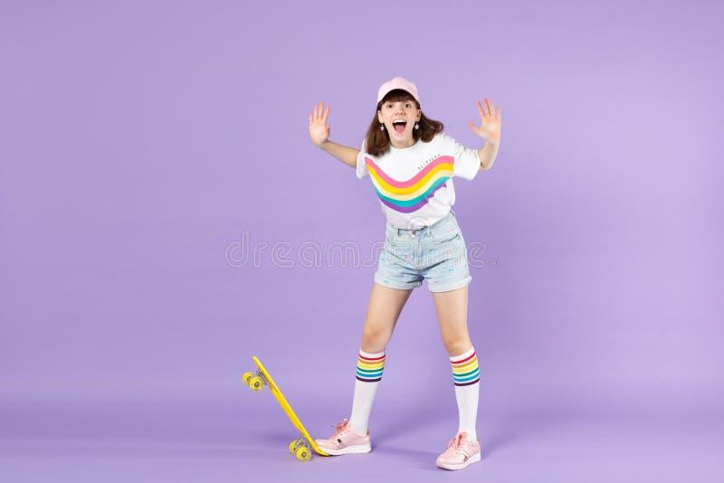 Κραυγάζοντας κορίτσι εφήβων στη ζωηρή στάση ενδυμάτων με τα κίτρινα skateboard χέρια διάδοσης που απομονώνεται στον ιώδη τοίχο κρ στοκ εικόνες
