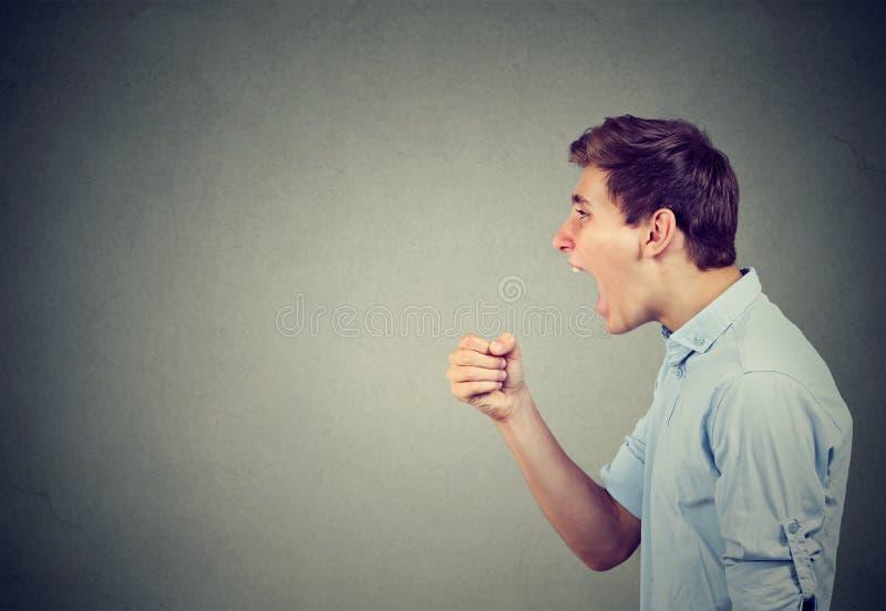 Κραυγάζοντας νεαρός άνδρας στο γκρίζο υπόβαθρο στοκ εικόνα με δικαίωμα ελεύθερης χρήσης