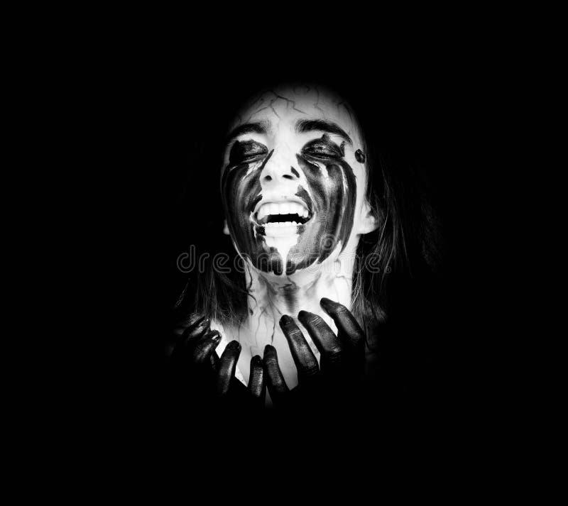 Κραυγάζοντας στο σκοτάδι, ένα τρελλό κορίτσι με τις μαύρες φλέβες στο πρόσωπό της έννοια αποκριών και ημέρα των νεκρών στοκ φωτογραφία