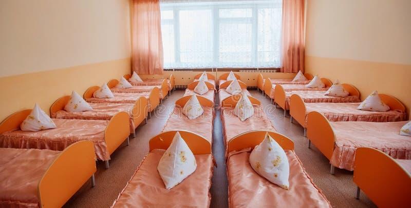 Κρεβάτια και κούνιες στο λαμπρά χρωματισμένο κοιτώνα ενός βρεφικού σταθμού Κούνιες πολλών παιδιών στοκ φωτογραφίες