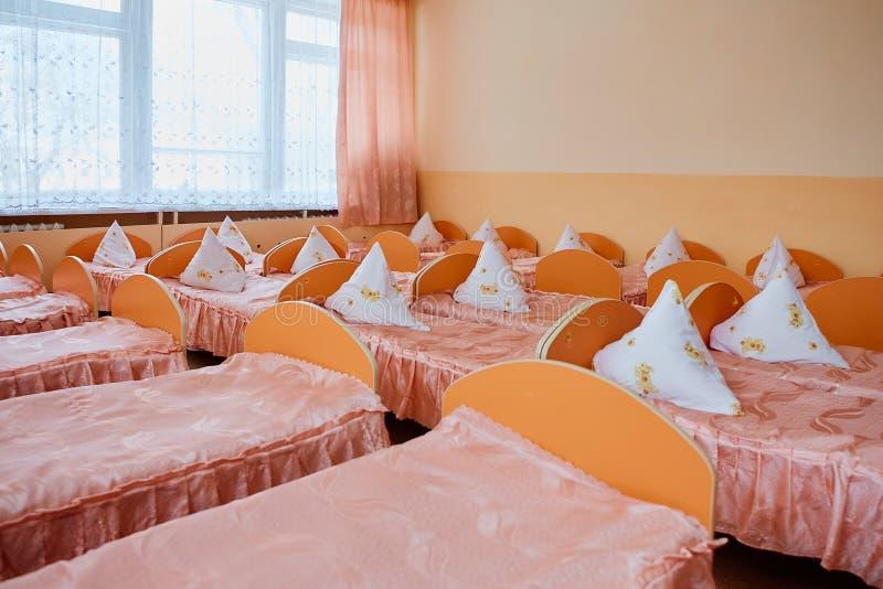 Κρεβάτια και κούνιες στο λαμπρά χρωματισμένο κοιτώνα ενός βρεφικού σταθμού Κούνιες πολλών παιδιών στοκ εικόνες