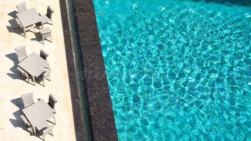 Κρεβάτια κόκκινου χρώματος και ήλιων ομπρελών θαλάσσης κοντά στην πισίνα πολυτέλειας με το μπλε νερό Έννοια διακοπών, τοπ άποψη στοκ εικόνες