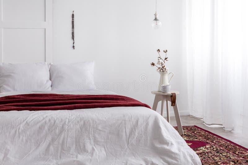 Κρεβάτι μεγέθους Toking με την άσπρη κλινοστρωμνή και το κόκκινο κάλυμμα στοκ εικόνα με δικαίωμα ελεύθερης χρήσης