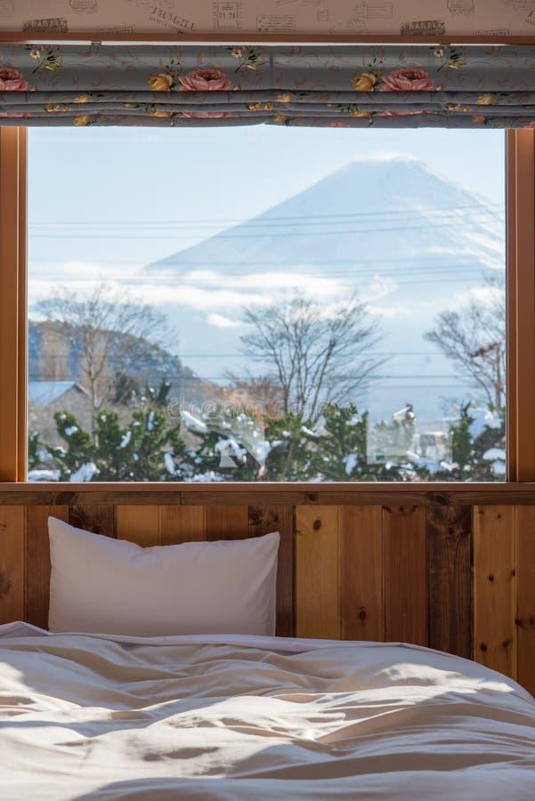 Κρεβάτι με την ΑΜ Άποψη του Φούτζι ως υπόβαθρο έξω από το παράθυρο στοκ φωτογραφίες