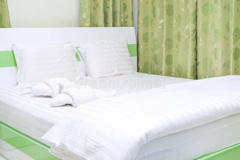 Κρεβάτι με τη διακοσμητική πετσέτα - πτυχές για να είναι πάπια στοκ εικόνα