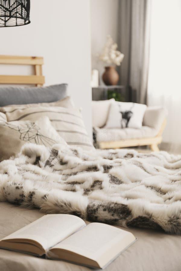 Κρεβάτι με το ανοικτά βιβλίο, τα μαξιλάρια και το coverlet γουνών στο εσωτερικό διαμερισμάτων Scandi με το θολωμένο υπόβαθρο στοκ φωτογραφίες με δικαίωμα ελεύθερης χρήσης