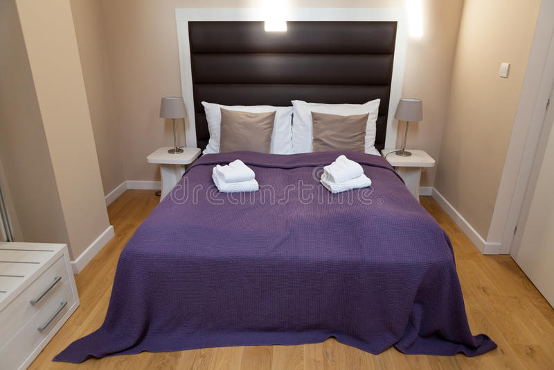 Κρεβατοκάμαρα με ένα ιώδες coverlet στοκ εικόνα