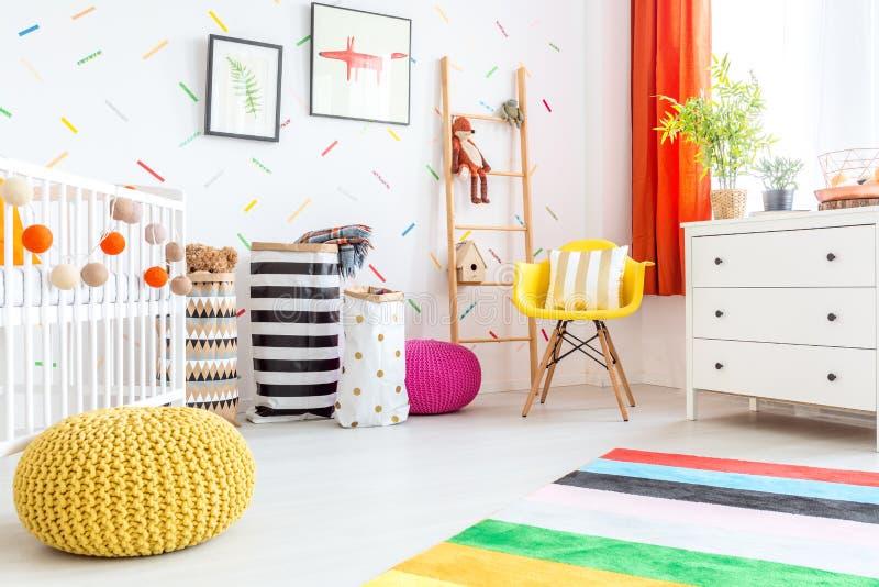 Κρεβατοκάμαρα μωρών με το κίτρινο μαξιλάρι πουφ στοκ φωτογραφία