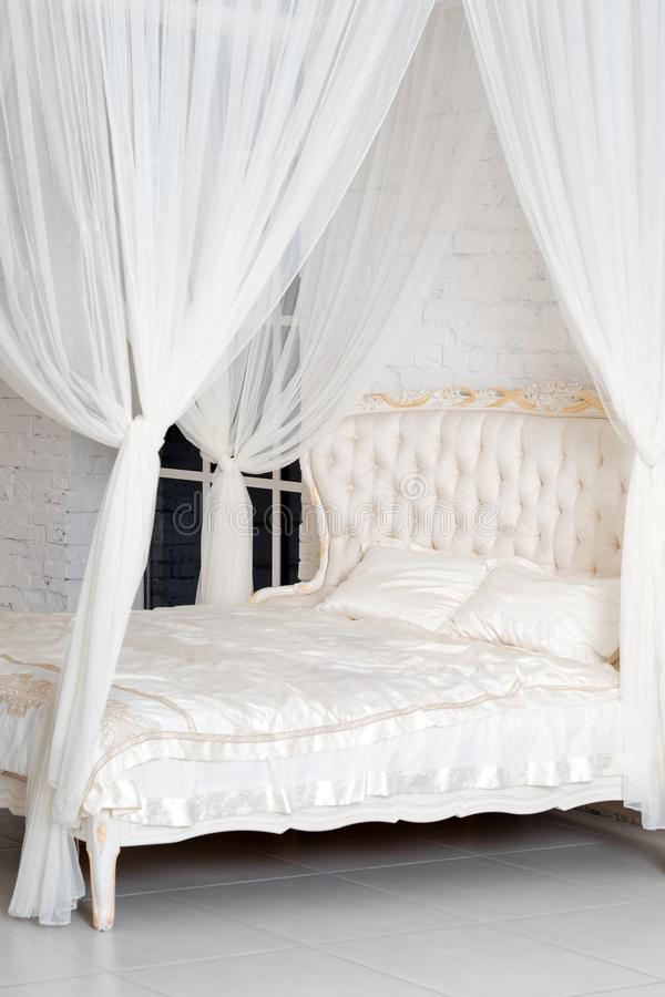 Κρεβατοκάμαρα στα μαλακά ελαφριά χρώματα Μεγάλο άνετο διπλό κρεβάτι τεσσάρων αφισών στην κομψή κλασική κρεβατοκάμαρα Λευκό πολυτέ στοκ εικόνα με δικαίωμα ελεύθερης χρήσης