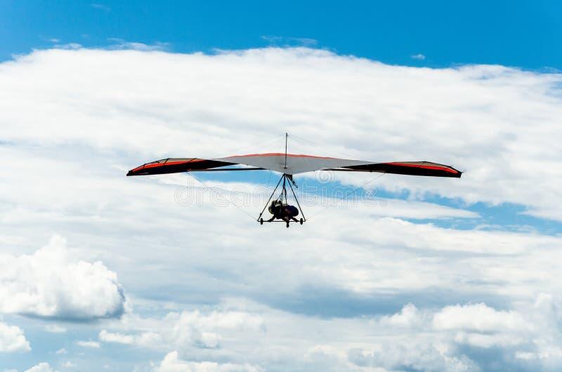 Κρεμάστε τη γλιστρώντας πτήση στο μπλε ουρανό με τα σύννεφα στοκ φωτογραφίες