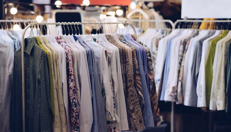 Κρεμάστρα καταστημάτων με τα νέα πουκάμισα ατόμων ` s στο κατάστημα μόδας στοκ εικόνες