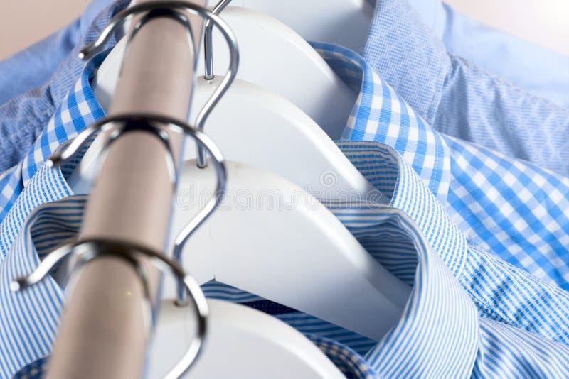 Κρεμάστρες υφασμάτων με τα πουκάμισα Ενδύματα ατόμων ` s στοκ φωτογραφίες με δικαίωμα ελεύθερης χρήσης
