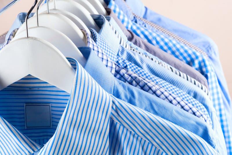 Κρεμάστρες υφασμάτων με τα πουκάμισα Ενδύματα ατόμων ` s στοκ φωτογραφίες